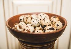 Los huevos de codornices están en las mercancías marrones en el fondo ligero Fotografía de archivo
