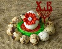 Los huevos de codornices y el huevo del pollo con el arco rojo están en un círculo alrededor del cuenco azul plástico de sal roja Foto de archivo libre de regalías