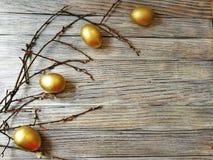 Los huevos de oro pintados en Pascua ligera con las ramitas del sauce en blanco envejecieron el fondo Foto de archivo libre de regalías