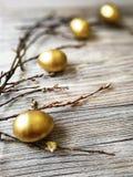 Los huevos de oro pintados en Pascua ligera con las ramitas del sauce en blanco envejecieron el fondo Imagenes de archivo