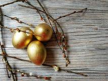 Los huevos de oro pintados en Pascua ligera con las ramitas del sauce en blanco envejecieron el fondo Fotos de archivo libres de regalías