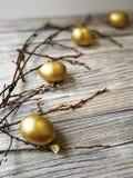 Los huevos de oro pintados en Pascua ligera con las ramitas del sauce en blanco envejecieron el fondo Imagen de archivo libre de regalías