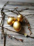 Los huevos de oro pintados en Pascua ligera con las ramitas del sauce en blanco envejecieron el fondo Imágenes de archivo libres de regalías