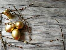 Los huevos de oro pintados en Pascua ligera con las ramitas del sauce en blanco envejecieron el fondo Foto de archivo