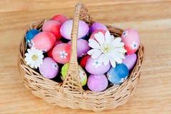 Los huevos de Pascua adornados con las margaritas remetieron adentro una cesta Imagen de archivo libre de regalías