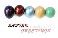 Los huevos de Pascua coloridos en el fondo blanco con la muestra mandan un SMS Fotografía de archivo
