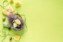 Los huevos de Pascua coloridos en pájaros jerarquizan con la decoración festiva en el fondo brillante del verde lima, imagen de foto de archivo libre de regalías