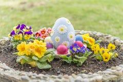 Los huevos de Pascua coloridos en una maceta con la violeta de cuernos florecen Imagen de archivo