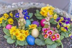 Los huevos de Pascua coloridos en una maceta con la violeta de cuernos florecen Fotografía de archivo