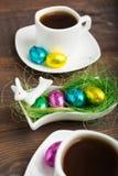 Los huevos de Pascua con el chocolate les gusta un postre con dos tazas de coffe Imagen de archivo