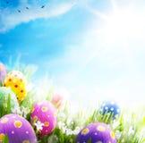 Los huevos de Pascua del arte adornaron el cielo azul de la hierba de las flores Foto de archivo