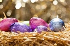 Los huevos de Pascua del chocolate en una paja natural jerarquizan Imagen de archivo