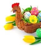 Los huevos de Pascua en cesta con el tulipán amarillo florecen Imagen de archivo