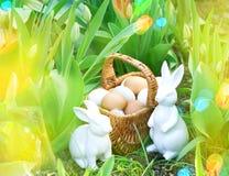 Los huevos de Pascua en cesta con el tulipán de la primavera florecen y los conejitos Fotografía de archivo libre de regalías