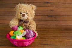 Los huevos de Pascua en cesta y juguete relleno llevan Foto de archivo libre de regalías