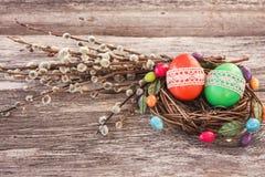 Los huevos de Pascua en pequeños jerarquía y sauce ramifican en fondo de madera Fotografía de archivo