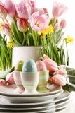 Los huevos de Pascua en tazas con el resorte florecen en blanco Imagen de archivo libre de regalías
