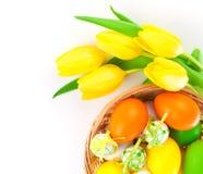Los huevos de Pascua en una cesta con los tulipanes amarillos florecen Imagen de archivo