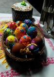 Los huevos de Pascua en una cesta de mimbre y una Pascua se apelmazan fotos de archivo libres de regalías