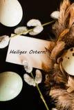 Los huevos de Pascua, la rama del sauce y las plumas jerarquizan en fondo negro Foto de archivo libre de regalías