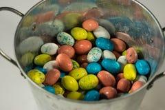 Los huevos de Pascua multicolores del caramelo en un metal bucket Fotografía de archivo