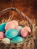 Los huevos de Pascua pintados con los guisantes mienten en una cesta Fotos de archivo