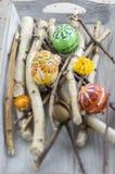 Los huevos de Pascua pintados hechos a mano hechos en casa en abedul ramifican en la bandeja de madera gris, huevos tradicionales Foto de archivo libre de regalías