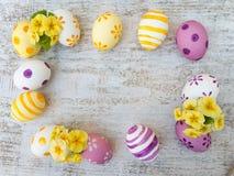 Los huevos de Pascua pintados y la primavera amarilla florece el marco Fotos de archivo