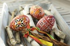 Los huevos de Pascua rojos hechos en casa y hechos a mano en abedul ramifican en la bandeja de madera, checo tradicional, caza de Imagenes de archivo