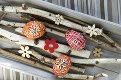 Los huevos de Pascua rojos hechos en casa y hechos a mano en abedul ramifican en la bandeja de madera, checo tradicional, caza de Fotos de archivo libres de regalías