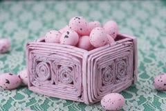 Los huevos de Pascua rosados en un rosa reciclaron la cesta de papel Fotos de archivo