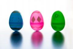 Los huevos de Pascua se levantan delante de todo el fondo blanco Imágenes de archivo libres de regalías