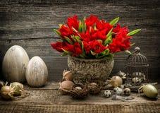 Los huevos de Pascua y el tulipán rojo florece la decoración del vintage Foto de archivo libre de regalías