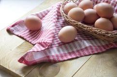 Los huevos del pollo de Brown están en la tabla, encendida por la luz del sol Fotografía de archivo libre de regalías