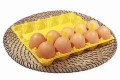 Los huevos del pollo en caja amarillean color en el fondo y la mecha blancos Foto de archivo libre de regalías