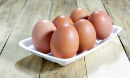 Los huevos en caja de la espuma en el fondo de madera Foto de archivo libre de regalías