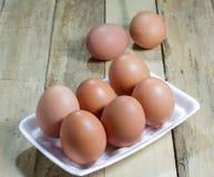 Los huevos en caja de la espuma en el fondo de madera Fotos de archivo libres de regalías