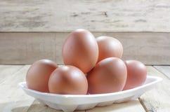 Los huevos en caja de la espuma en el fondo de madera Fotografía de archivo libre de regalías