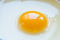 Los huevos en un cuenco con los batidores acercan a la yema de huevo Imagenes de archivo