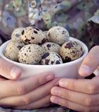 Los huevos en un tazón de fuente en las muchachas traslapan. Fotografía de archivo libre de regalías
