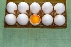 Los huevos en una caja plástica marrón oscura en un fondo verde con un espacio de la copia abajo, uno de docena huevos están queb imagen de archivo
