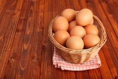 Los huevos frescos del pollo en la cesta pusieron el mantel del vintage Fotos de archivo