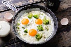 Los huevos fritos del sartén con el fondo del bróculi y de madera Fotografía de archivo libre de regalías