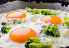Los huevos fritos del sartén con el fondo del bróculi y de madera Imagen de archivo
