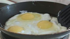 Los huevos fritos interfieren con una espátula en una cacerola a cámara lenta almacen de video