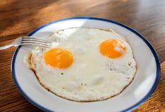 Los huevos fritos les gusta una cara sonriente en la bandeja con el disco azul claro Foto de archivo