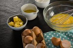 Los huevos, la bandeja del huevo, la mantequilla, el aceite y la harina batidos guardaron en una superficie negra Foto de archivo