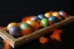 Los huevos multicolores pintados para Pascua mienten en una bandeja de oro fotografía de archivo