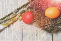 Los huevos pintados coloridos en pájaro jerarquizan en el fondo de madera, pascua Imagen de archivo libre de regalías