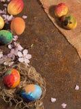 Los huevos pintados a mano y la lona franjada del yute, flor de la almendra y pétalos de Pascua, arreglaron en textura rústica ox Foto de archivo